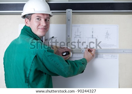 an engineer standing by the adjustable drawing board with a pencil