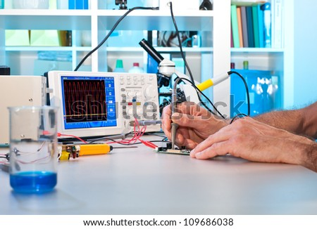 An engineer tests electronic components with oscilloscope in the service centre