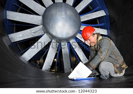 An engineer, wearing a hardtop, going through his notes in front of a huge industrial wind tunnel rotor