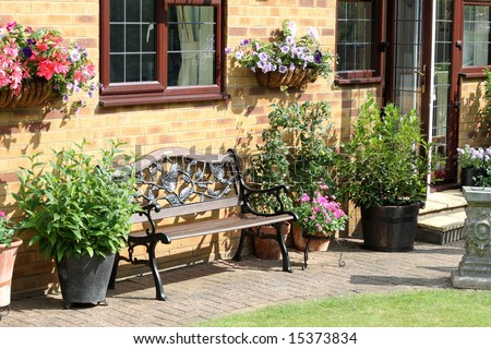 An English Back garden with bench seat, flower filled wall baskets and flowerpots