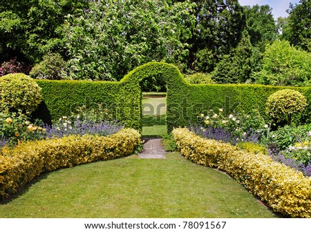 An English Landscape Garden in early Summer with flowerbeds and an Arch through a Hedgerow