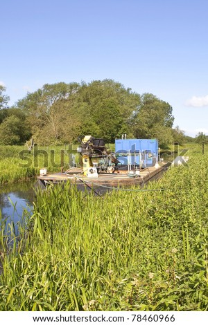 an english landscape with a small dredger at its moorings near a lock on a rural canal under a summer sky