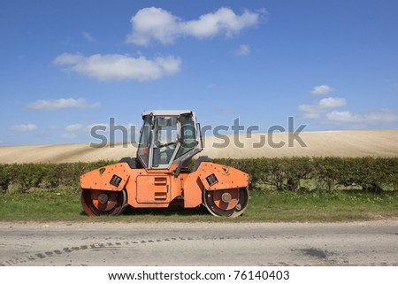 an english landscape with an orange roller with damaged window parked by a country road with hedgerows and arable fields under a blue sky with fluffy white clouds