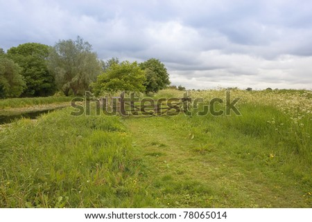 an english landscape with wooden gate surrounded by lush wildflowers on a rural footpath under stormy skies