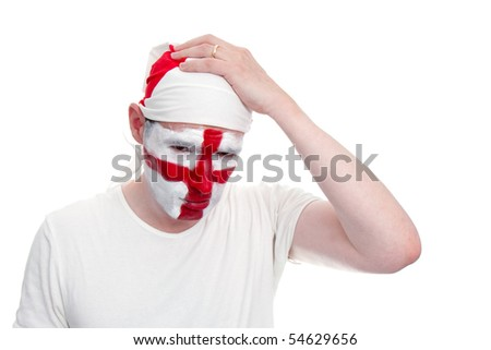 An English sports fan holds his hand on his head whilst looking upset.  The fan has an England flag bandana and his face painted with the England flag.   Studio isolated on white.