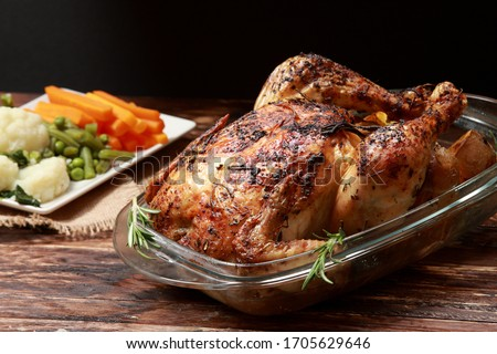 An English Sunday Roast Chicken marinated with herbs and spices and served with Roast Potatoes and Vegetables as side dish Stockfoto ©