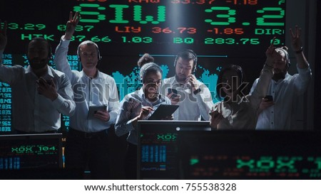 An enthusiastic stock broker team in a futuristic office full of live global market feeds.