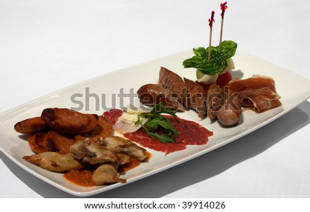 An Entree selection plate offering Roasted Quail, Italian Sausages, Beef Carpaccio, Prosciutto, Tomato, and Bocconcini