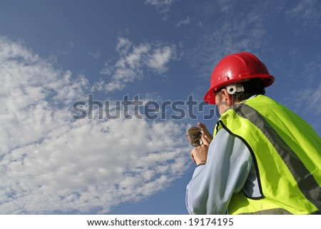 An environmental engineer examining a sample showing the beautiful blue sky, wearing an yellow reflective vest and red safety helmet.