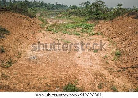 An environmental problem caused by water scarcity with a dry river bed without any water in the green but dry landscape of Bangladesh #619696301