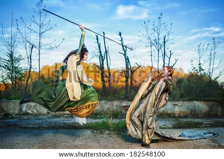 Stock Photo An epic scene - a female assassin attacks a terrified woman in royal attire with a spear.