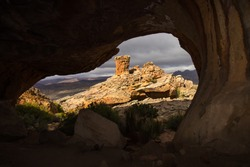An eroded sandstone pillar framed by the entrance of a small cave in the Cederberg Mountains of South Africa