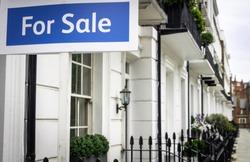An estate agent 'For Sale' sign on upmarket London street