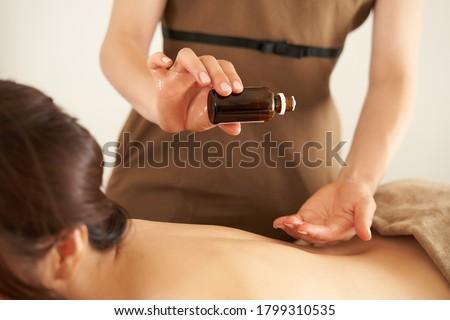 An esthetician dripping massage oil at an aesthetic salon ストックフォト ©