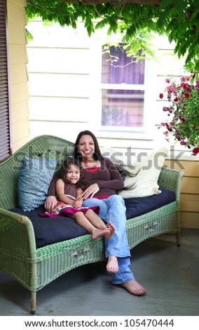 An ethnic mother and daughter snuggle on a wicker couch on a porch on a sunny day.