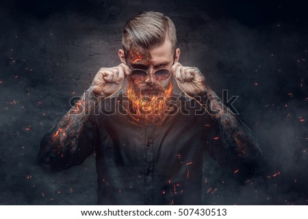 An evil man with burning beard in fire sparks and smoke. Halloween 31 October.