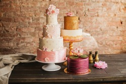 An example of three beautiful wedding cakes from a pastry chef. Elegant and unusual design with edible gold and sugar flowers.