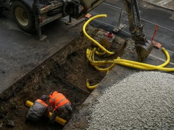 An excavator and two diggers dig a trench to lay a drainage pipe across a public road. underground corrugated pipe laying