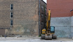 An excavator (backhoe) is parked in an empty lot behind two brick buildings.
