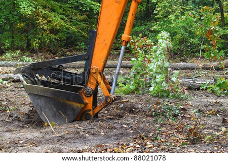 An Excavator bucket with the jaw attachment on it used for lifting trees and debris resting on the ground outside in the woods.