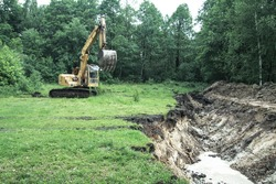 An excavator digs a large trench for building a house. A tractor digs a large lake that is already gaining water.
