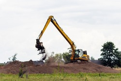 An excavator in the summer compares the shores of a freshly dug pond