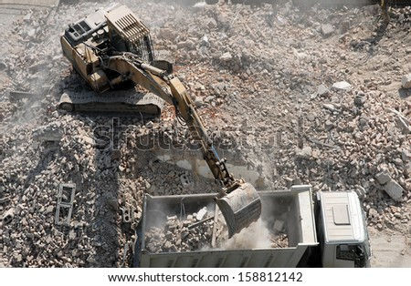 An excavator loading a truck after demolishing houses for reconstruction #158812142