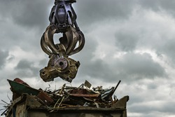 An excavator loads scrap metal into the back of a truck at a landfill or recycling center.