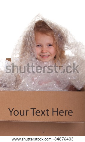 An excellent image of a cute child being packaged up into a shipping box.
