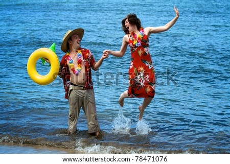An excited couple on vacation frolic in the waves on a beach in Maui, Hawaii.