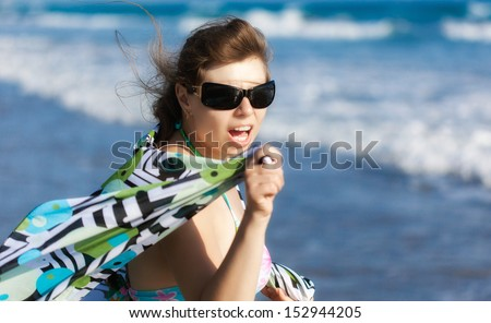 An exciting woman is on the beach. Great emotion on her face