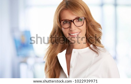 An executive attractive businesswoman with toothy smile standing at the boardroom after business meeting. #1022939971