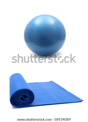 An exercise mat and a fitball isolated against a white background
