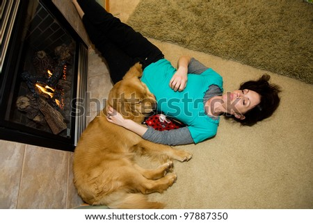 An exhausted woman sleeping comfortably next to a fire with her Golden Retriever dog.