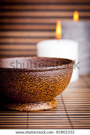 An exotic Asian style wooden bowl on bamboo with candles