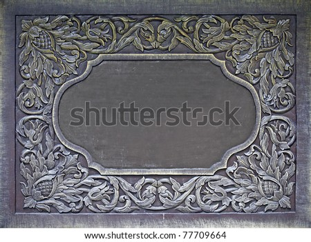An exotic floral carving border on a hardwood timber panel with blank space for copyspace text.