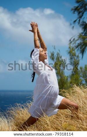 An exotic Hawaiian woman in a flowing white dress does a yoga pose in the tall grass overlooking the ocean on Maui, Hawaii. Vertical image orientation.