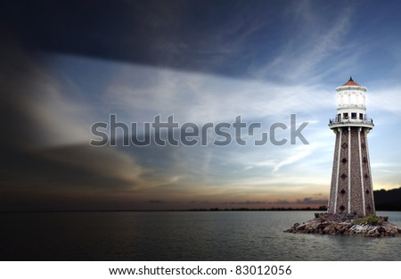 An exotic lighthouse shinning its torch on an outcrop of rocky reef located near a remote tropical coastal beach in Langkawi Island, during a surreal sunset.