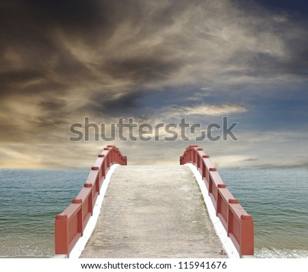 An exotic masonry bridge leading into the horizon of a turquoise sea against a surreal dramatic sunset.