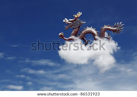 An exotic oriental mythical dragon flying on a fluffy cloud across a blue sky. The dragon is the fifth zodiac sign in the Chinese horoscope and for year 2012.