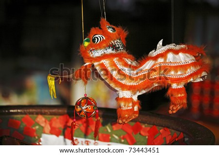 An exotic string puppet of a colorful oriental Lion dance costume.