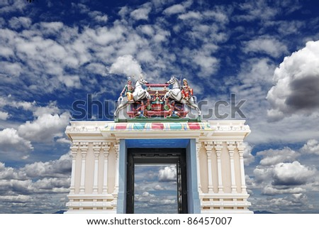 An exotic vintage Hindu temple archway decorated with colorful religious horse ornaments against a serene blue cloudy sky.