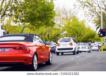 An expensive top-class beautiful red cabriolet driving on a city road among other affordable general cars