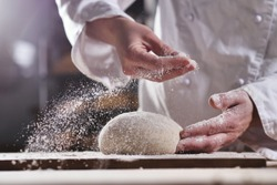 An experienced chef in a professional kitchen prepares the dough with flour to make the bio Italian pasta. the concept of nature, Italy, food, diet and bio.