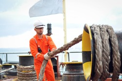 An experienced sailor in orange overalls and a white helmet works on a bulk carrier.