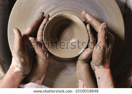 An expert potter, he creates with clay and his hands a beautiful vase in his laboratory. The artisan creates works of art with his hands. Concept of: experience, art, tradition, clay.
