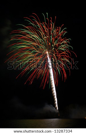 An explosion of red and green fireworks in the dark night sky