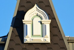 An exquisite window on a turret on the roof of a new building in the traditional Russian style. Provincial Art Nouveau in Architecture.