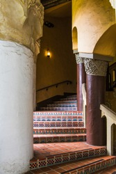 An exterior stairway in  an old Spanish architectural style with beautiful tiles with complex patterns curves through columns in an historic building in Santa Barbara, California, USA