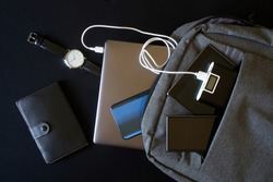 An external battery - power bank and many modern gadgets: smartphones, laptop and tablet are in a trendy gray city backpack. Charge your gadgets while traveling and trip. Black background. Close-up